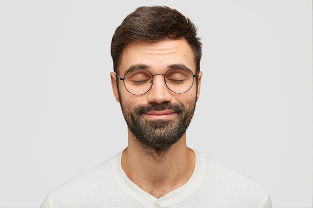 Довольный молодой человек закрывает глаза и представляет себе что-то приятное, мечтает о невероятных вещах