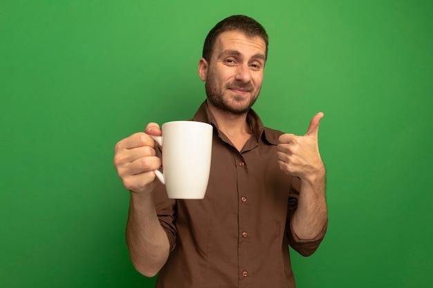 벽을 엄지 손가락을 보여주는 차 한잔 들고 녹색에 고립 된 기쁘게 젊은 남자