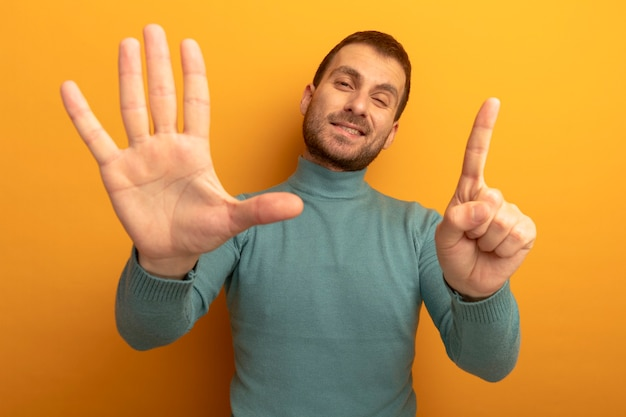 Pleased young man looking at front winking showing six with hands isolated on orange wall