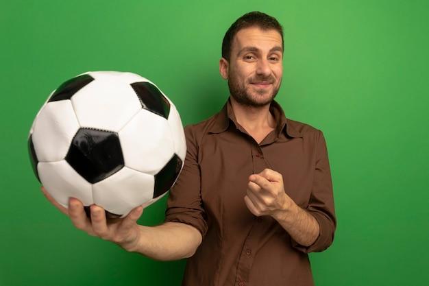 녹색 벽에 고립 된 공을 가리키는 카메라를보고 앞으로 축구 공을 뻗어 기쁘게 젊은 남자