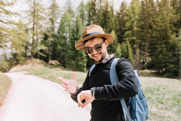Felice giovane uomo in occhiali da sole guardando l'orologio da polso con il sorriso in piedi sulla strada sulla natura