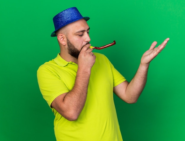 Pleased young man wearing blue party hat blowing party whistle raising hand isolated on green wall