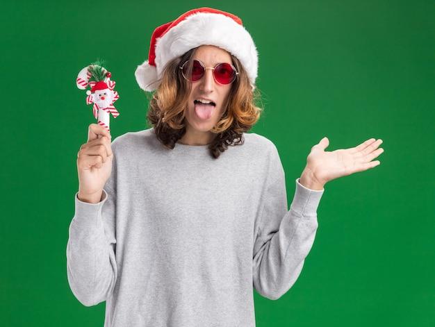 クリスマスのサンタの帽子とクリスマスのキャンディケインを保持している赤い眼鏡を身に着けている若い男は、緑の背景の上に立っている手の腕を提示して幸せで陽気な舌を突き出して喜んでいます