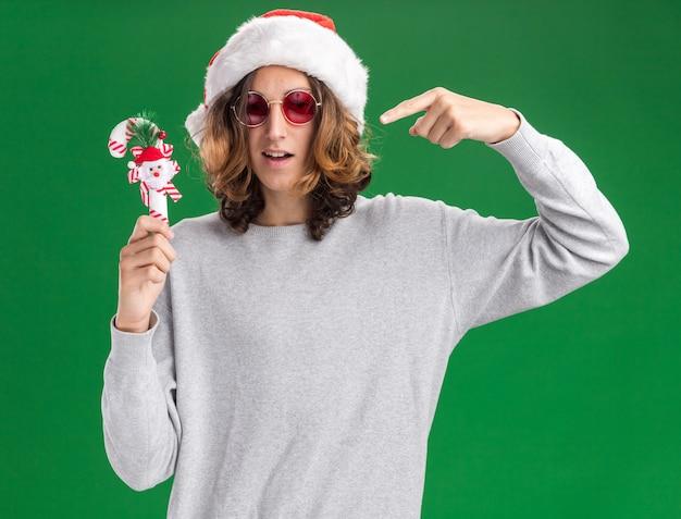 クリスマスのサンタの帽子と赤い眼鏡を身に着けている若い男は、緑の背景の上に立っているそれで人差し指を指して笑顔のクリスマスキャンディケインを持って喜んで
