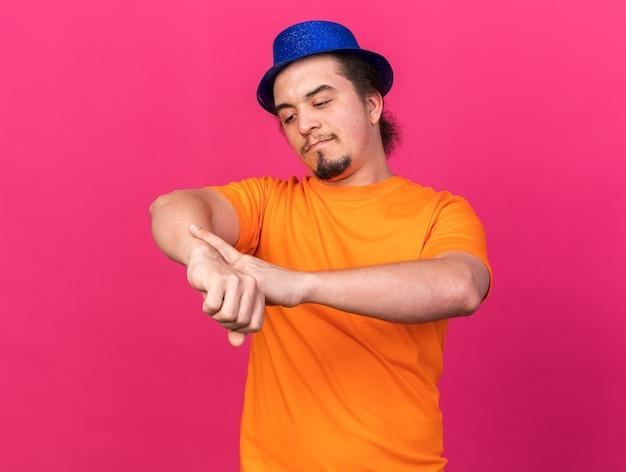 パーティーハットをかぶって、ピンクの壁に分離された手首の時計のジェスチャーを示す喜んで若い男