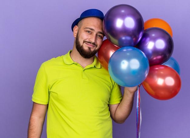 風船を持ってパーティハットをかぶって喜んで若い男