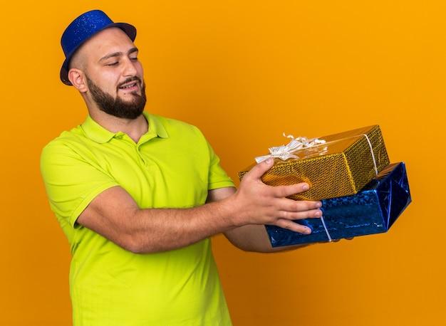 Довольный молодой человек в партийной шляпе, протягивая подарочные коробки сбоку
