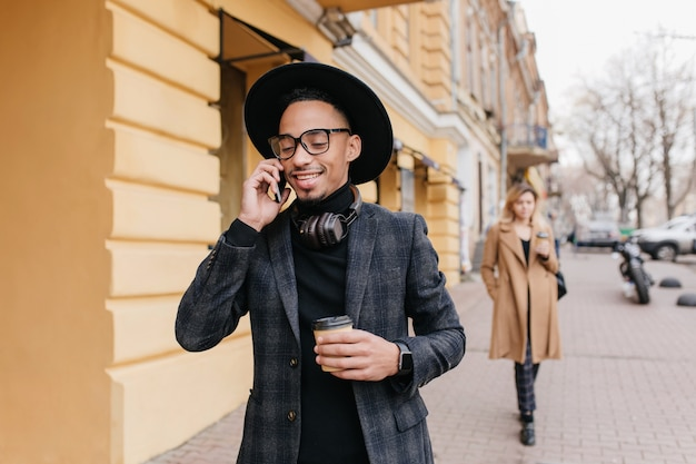 거리에서 커피를 마시는 갈색 피부를 가진 기쁘게 젊은 남자. 누군가 전화하는 라떼 한잔과 함께 행복 한 아프리카 남자.