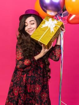 풍선을 들고 있는 파티 모자를 쓰고 분홍색 벽에 눈을 감고 있는 선물 꾸러미와 얼굴을 만지는 선물 꾸러미를 입은 행복한 젊은 파티 소녀