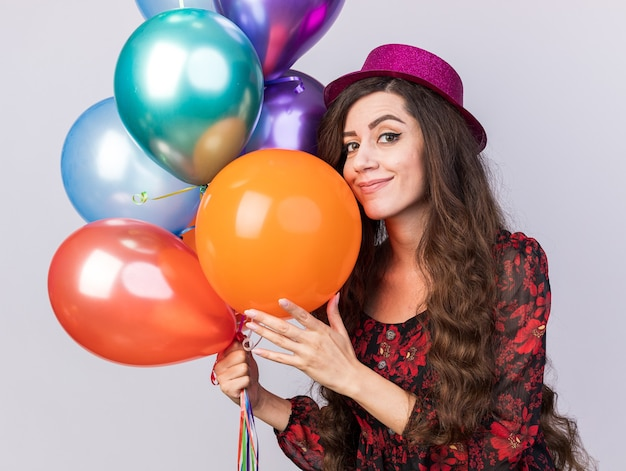 Pleased young party girl wearing party hat holding and touching balloons looking at camera isolated on white wall