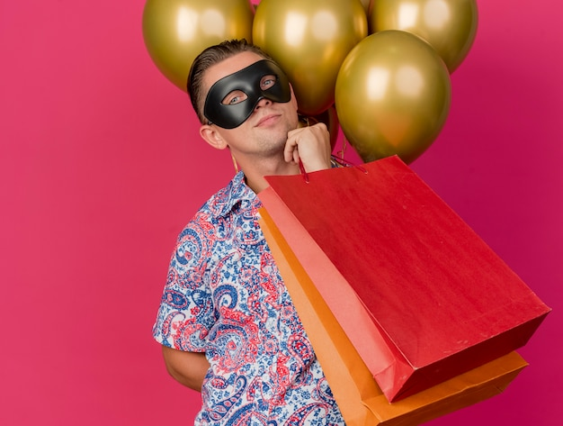 Pleased young party guy looking at camera wearing masquerade eye mask standing in front of balloons holding gift bags putting hand on chin isolated on pink background