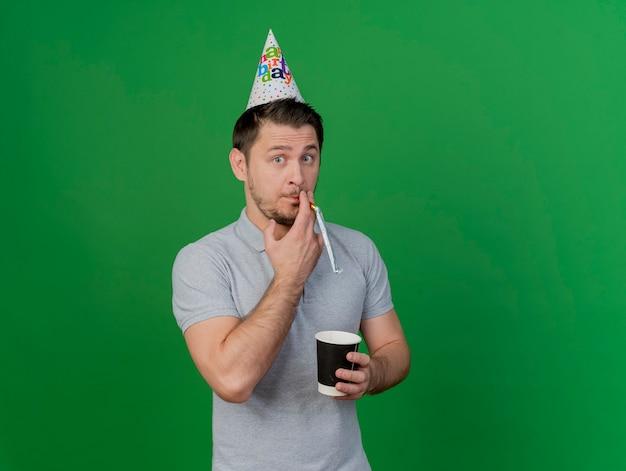Довольный молодой тусовщик в кепке дня рождения дует в свисток с чашкой кофе, изолированной на зеленом