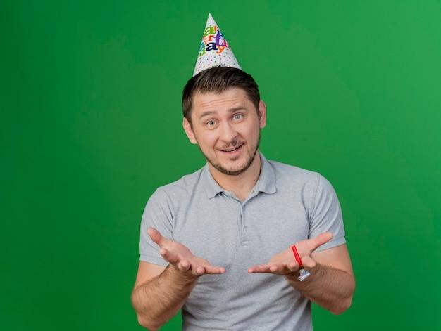 パーティーブロワーを保持し、緑に分離された手を差し出して誕生日キャップを身に着けている若いパーティーの男を喜ばせる 無料写真