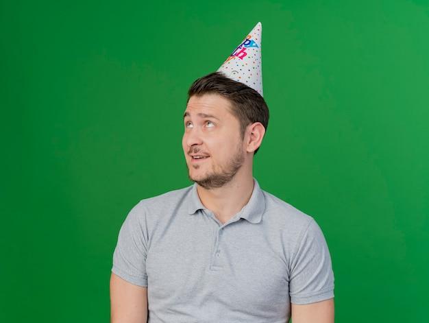 緑で隔離の誕生日キャップを身に着けている若いパーティーの男を喜ばせる