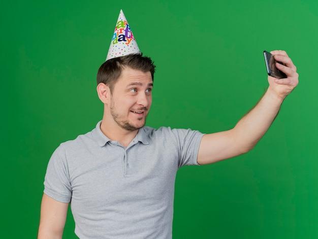 誕生日の帽子をかぶって喜んで若いパーティーの男は、緑に分離されたセルフィーを取る