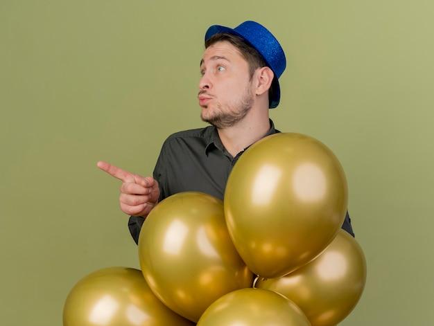 올리브 그린에 고립 된 측면에서 풍선과 포인트 뒤에 서 검은 셔츠와 파란색 모자를 입고 기쁘게 젊은 파티 남자
