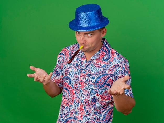 Довольный молодой тусовщик в синей шляпе дует вентилятор и протягивает руки к камере, изолированной на зеленом фоне