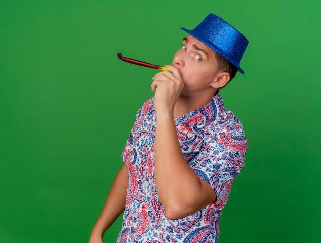 Довольный молодой тусовщик в синей шляпе дует вентилятор, изолированный на зеленом