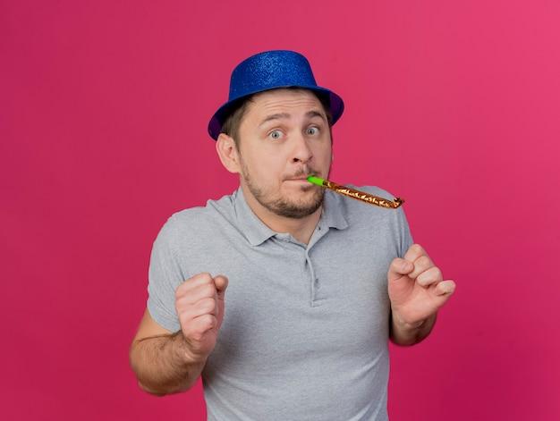 Довольный молодой тусовщик в синей шляпе дует вентилятор, изолированный на розовом