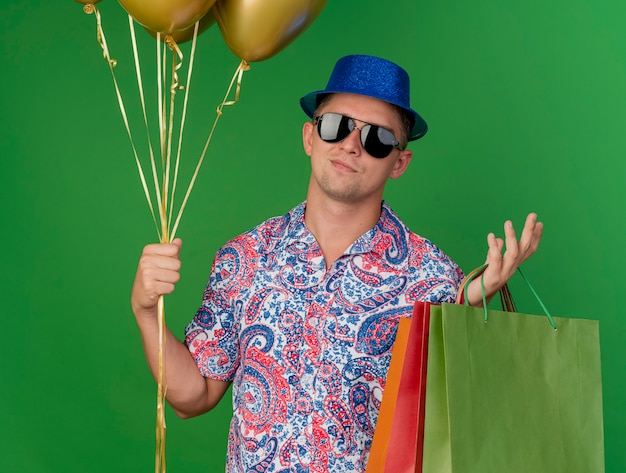 Pleased young party guy wearing blue hat and glasses holding balloons with gift bags and spreading hand isolated on green background