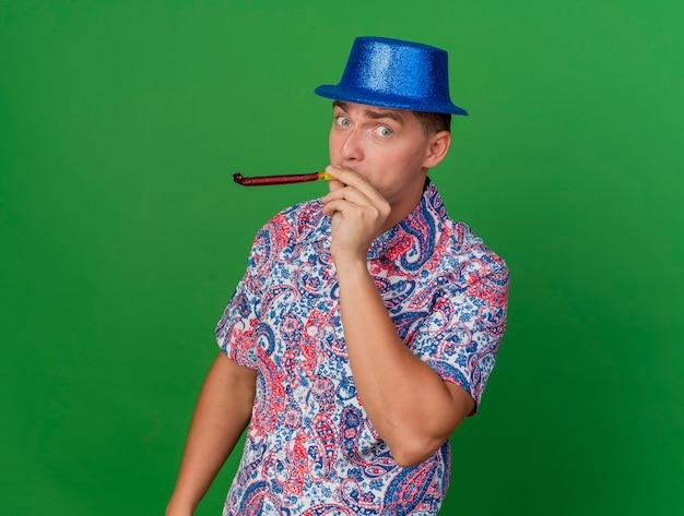 Довольный молодой тусовщик в синей шляпе держит и дует вечеринку, изолированную на зеленом