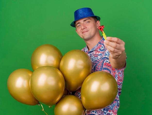 風船を保持し、緑に分離されたパーティーブロワーを差し出す青い帽子をかぶって喜んで若いパーティー男