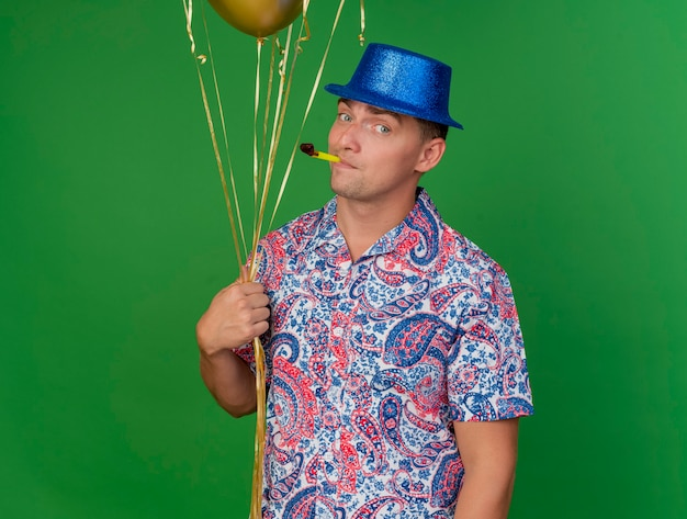 Довольный молодой тусовщик в синей шляпе держит воздушные шары и кладет в рот вентилятор, изолированный на зеленом