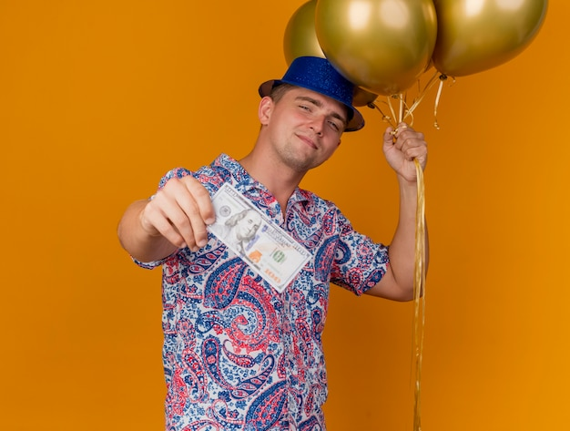 Pleased young party guy wearing blue hat holding balloons and holding out cash isolated on orange