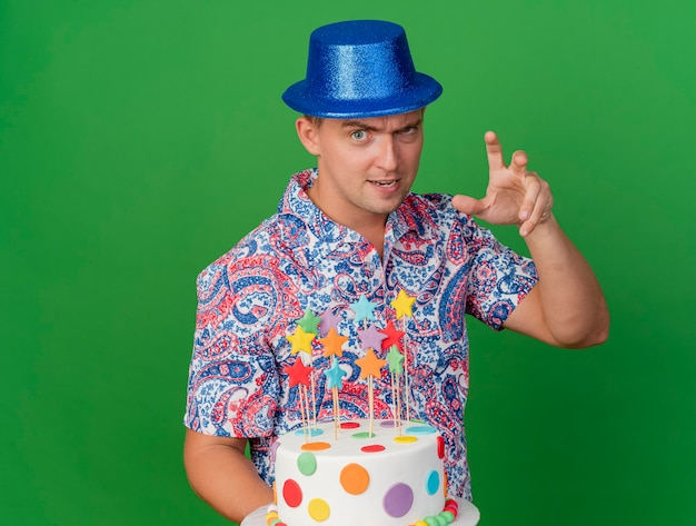 Pleased young party guy wearing blue hat holding cake showing tiger style gesture isolated on green