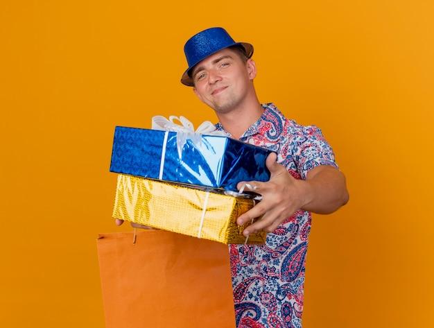 오렌지에 고립 된 가방과 함께 선물 상자를 들고 파란색 모자를 쓰고 기쁘게 젊은 파티 남자