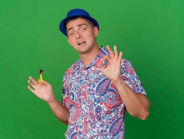 Довольный молодой тусовщик в синей шляпе, держащий воздуходувку, показывающий нормальный жест, изолированный на зеленом