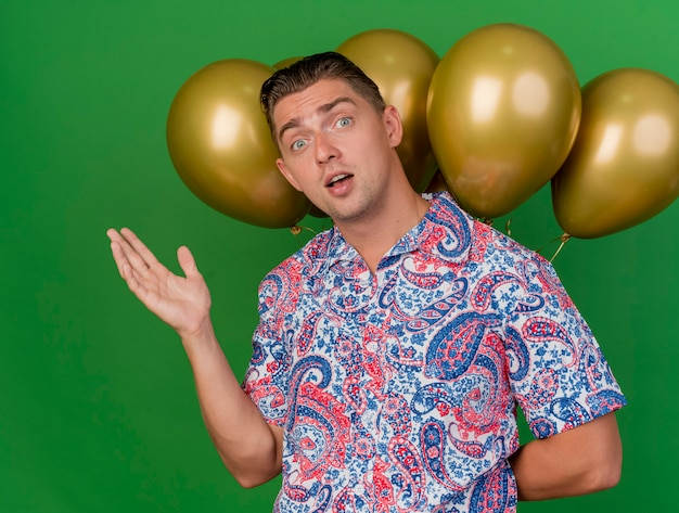 Pleased young party guy wearing blue hat standing in front of balloons points with hand at side isolated on green background