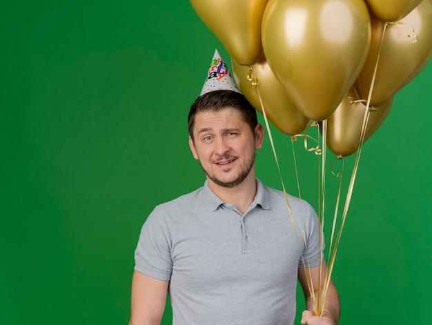 緑で隔離の風船を保持している灰色のシャツと誕生日の帽子を身に着けている若いパーティーの男を喜ばせる