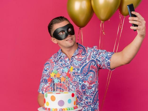 ケーキと風船を保持し、ピンクで隔離のセルフィーを取る仮面舞踏会のアイマスクを身に着けている若いパーティーの男を喜ばせる
