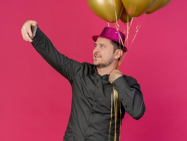風船を持ってピンクの帽子をかぶって喜んでいる若いパーティーの男はピンクで隔離されたselfieを取る