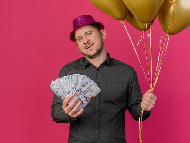 Pleased young party guy wearing pink hat holding cash with balloons isolated on pink
