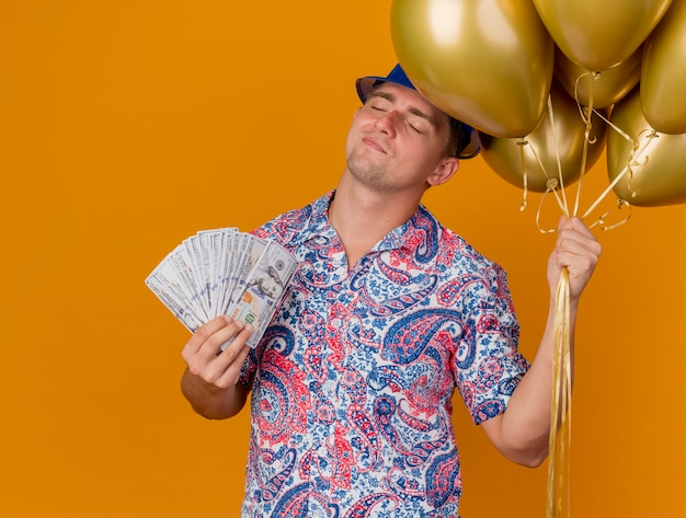 Pleased young party guy with closed eyes wearing blue hat holding balloons and cash isolated on orange