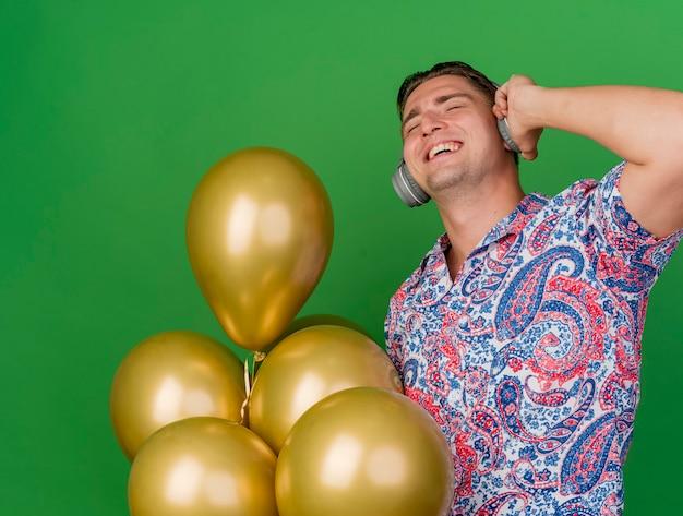 화려한 셔츠와 녹색 배경에 고립 된 풍선을 들고 헤드폰을 착용하는 닫힌 눈을 가진 기쁘게 젊은 파티 남자
