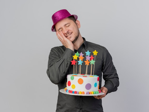 Pleased young party guy with closed eyes wearing pink hat holding cake putting hand on face isolated on white background