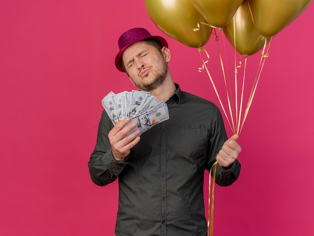 Pleased young party guy with closed eyes wearing pink hat holding cash with balloons isolated on pink