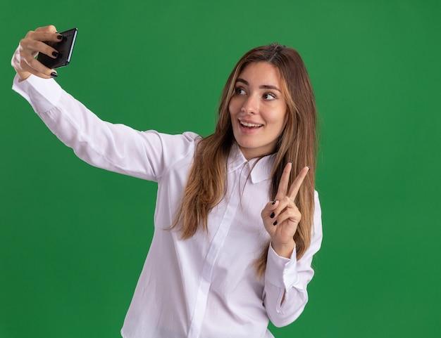 Lieta giovane ragazza abbastanza caucasica gesti il segno della mano di vittoria che tiene e guardando il telefono prendendo selfie sul verde