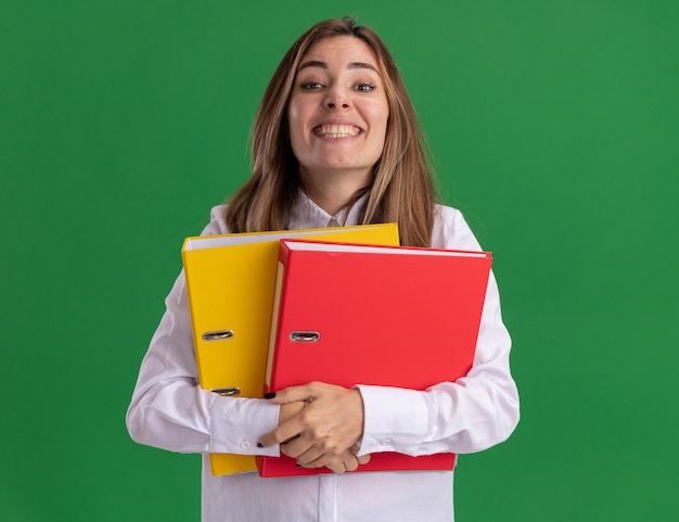 Pleased young pretty caucasian girl holds file folders on green