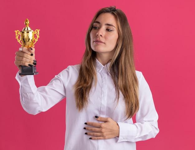 La giovane ragazza abbastanza caucasica soddisfatta tiene ed esamina la tazza del vincitore sul colore rosa