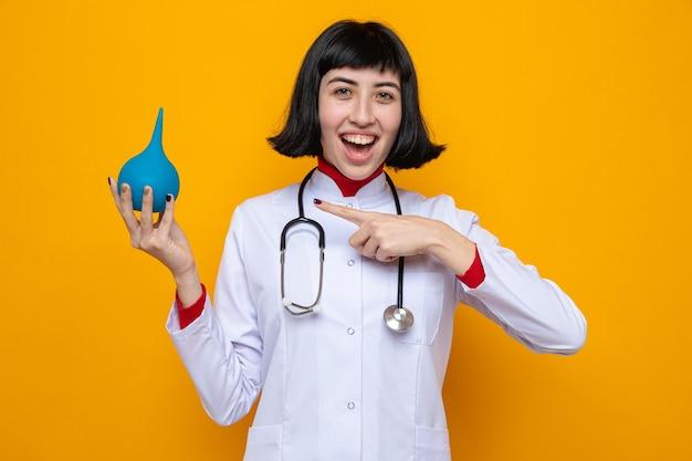 청진기를 들고 관장기를 가리키는 의사 제복을 입은 젊은 백인 소녀를 기쁘게 생각합니다.