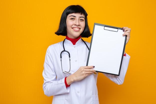 クリップボードを保持している聴診器で医者の制服を着た若いかなり白人の女の子を喜ばせる