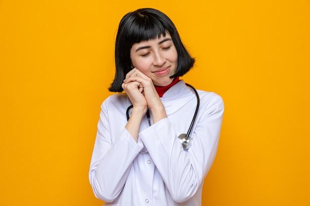 의사 유니폼을 입은 젊은 백인 소녀가 눈을 감고 손을 잡고 서 있는 것을 기쁘게 생각합니다.