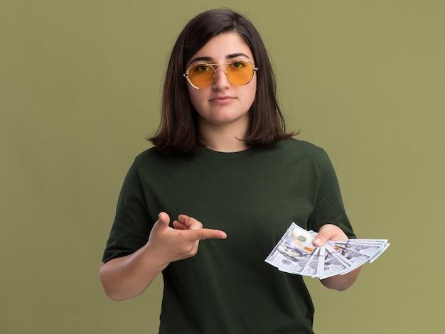 Довольная молодая симпатичная кавказская девушка в солнцезащитных очках держит и указывает на деньги, изолированные на оливково-зеленой стене с копией пространства