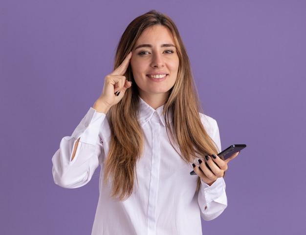 La giovane ragazza abbastanza caucasica soddisfatta mette il dito sulla tempia e tiene il telefono