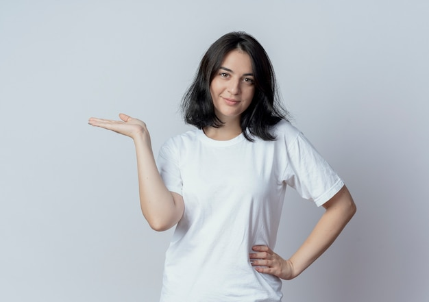 Pleased young pretty caucasian girl putting hand on waist and showing empty hand isolated on white background