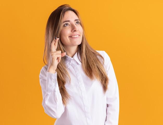 Довольная молодая симпатичная кавказская девушка стоит со скрещенными пальцами, глядя вверх